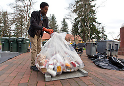 Ryan Grant weighs a bag of recyclables during Garbology on Red Square, where grash from different locations is sorted to determine how much is recycleable or compostable at PLU on Tuesday, March 17, 2015. (Photo: John Froschauer/PLU)