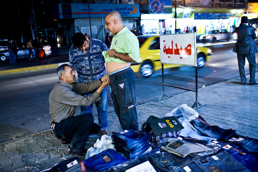 Men shop for pants on the sidewalks in Karadah district, Baghdad in Iraq.