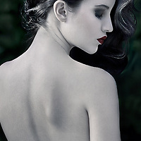 A young woman with long black hair wearing a backless dress with face in profile