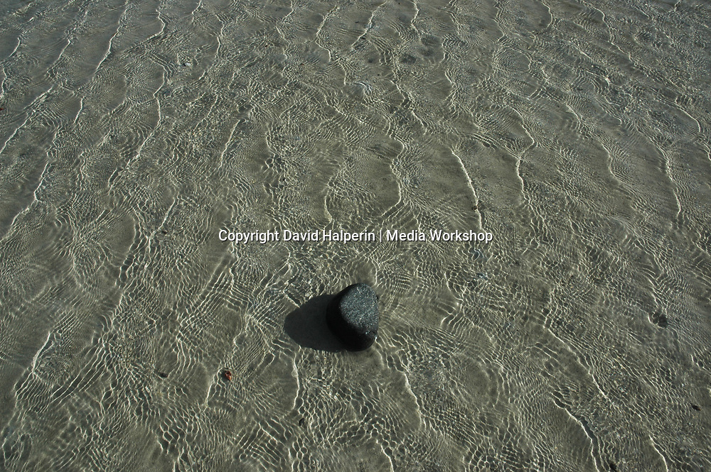 A single black stone sits on sand in rippled water. Zen-like simplicity.