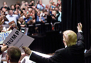 February 21, 2016 - Atlanta, Georgia: Coming on the heels of his South Carolina primary win, Donald Trump visited Atlanta on Sunday to address an estimated 10,000 supporters at the Georgia World Congress Center.<br /> <br /> Over the course of roughly an hour, the GOP presidential hopeful covered a variety of topics. He claimed he would force Mexico to build a wall along the U.S. border, boasted of his negotiating skills, and denigrated the media.<br /> <br /> Early on in the talk, the spotlight on Trump went dark. The real estate tycoon, whose bid to become the GOP presidential nominee has managed to last longer than many political observers expected, then told the crowd he would not pay for the room. When the lights were turned back on, Trump said he preferred to speak without the spotlight. He did.<br /> <br /> Before Trump spoke, a voice over a loud speaker said the event was private and funded by the candidate and that protesting would not be allowed. During Trump&rsquo;s speech, a protester wearing a pro-immigrant t-shirt interrupted the event. The man was escorted out of the ballroom.