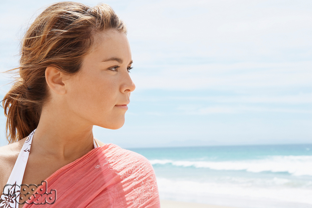 Young woman standing on beach close-up head and shoulders