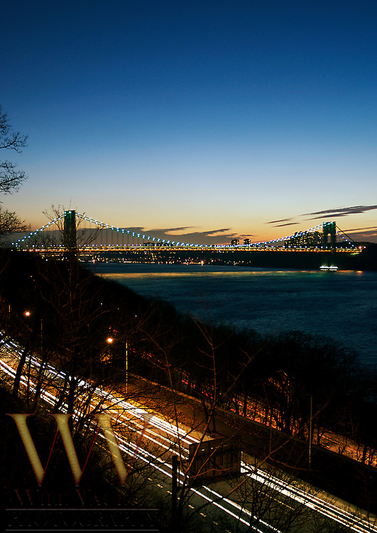 Long exposure light streaks from cars on highway with the George Washington Bridge in the distance.