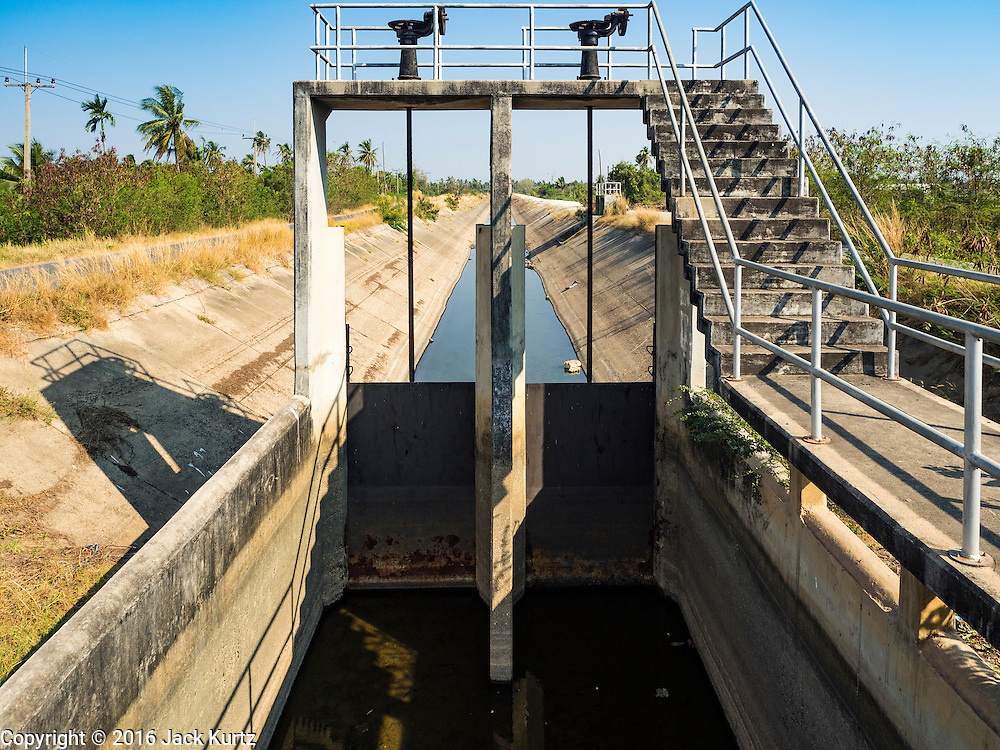 01 MARCH 2016 - CHACHOENGSAO, THAILAND: The water gate at a nearly empty irrigation canal in Chachoengsao province of Thailand. Thai government officials have warned that there may not be enough water in the country's reservoirs to provide adequate water for farming, including fish and shrimp farms, industrial needs and domestic consumption. The government has told rice and fish farmers to reduce their use of water, and if necessary to reduce their crops. The current El Niño weather pattern is being blamed for the drought. The 2015 rainy season was well below normal and the 2016 rainy season could start two months late.    PHOTO BY JACK KURTZ