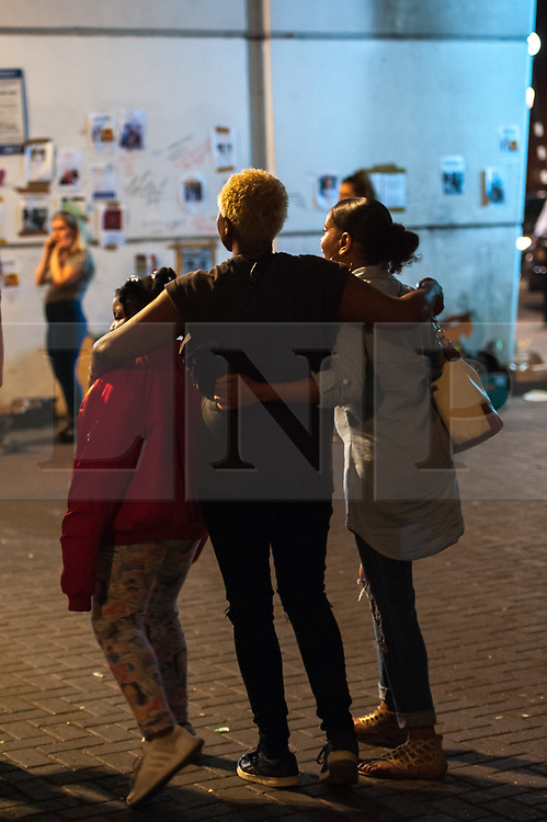 © Licensed to London News Pictures. 16/06/2017. London, UK. A group of women embrace at a late night vigil for the victims of the Grenfell tower block in west London earlier this week. The blaze engulfed the 27-storey building killing 12 - with 34 people still in hospital, 18 of whom are in critical condition. The fire brigade say that they don't expect to find anyone else alive. Photo credit: Guilhem Baker/LNP