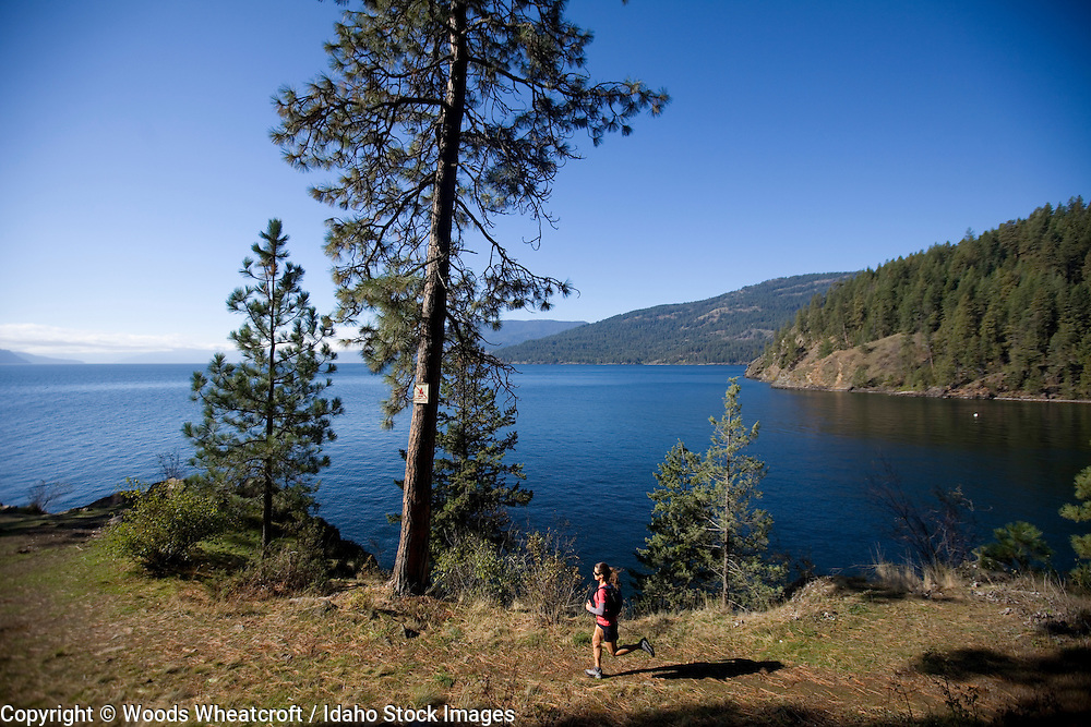 Adult woman trail running at Mineral Point near Sandpoint, Idaho.