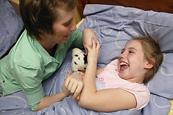 Single parent tickling her young daughter at bedtime,