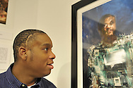 "Hasheem Kirkland, a vision impaired photographer, facing his photograph ""Cyborg"" at Artist Reception for Seeing with Photography Collective SWPC a group of visually impaired, sighted and totally blind photographers based in NYC, on Saturday, April 28, 2012, at African American Museum, Hempstead, New York, USA, and hosted by Long Island Center of Photography. Aperture published the group's ""Shooting Blind: Photographs by the Visually Impaired"" in 2005."