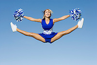 Smiling Cheerleader jumping in mid-air (portrait)