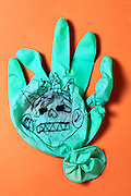 broken green rubber glove with a children drawing