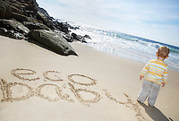 Boy (1-2) standing by Eco Baby text written on beach