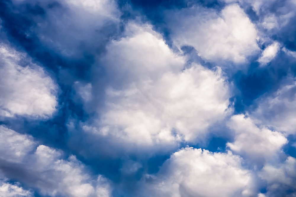 Puffy white clouds with dark blue sky.