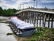 09 AUGUST 2018 - BAN LAEM, PHETCHABURI, THAILAND: Royal Thai Navy boats arrayed across the Phetchaburi River in Ban Laem. The navy uses the propellers on the boats to push flood water down river in the event of flooding. The boats have been pre-positioned on the river because it is expected to flood this week. The Phetchaburi River flows from Kaeng Krachan Dam to the Gulf of Siam through several towns including Ban Lat, Phetchaburi (the capital of Phetchaburi province) and Ban Laem. Government officials have warned residents of those towns that their towns will flood because the reservoir behind the dam is approaching capacity. Ban Lat and Phetchaburi could be flooded for several weeks. Residents of Ban Laem have been warned that their community could be inundated for over a month. Dams in Kanchanaburi province, west of Phetchaburi, are also approaching capacity and flooding is expected in that area also.   PHOTO BY JACK KURTZ