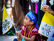 27 NOVEMBER 2017 - YANGON, MYANMAR: A child with a Vatican flag waits to see Pope Francis on his motorcade route into Yangon. Pope Francis arrived in Yangon Monday for a four day / three night visit. Tuesday he is going to the capitol, Naypyidaw (Nay Pyi Taw) to meet with Aung San Suu Kyi and other Myanmar leaders. Wednesday and Thursday he is saying mass in Yangon and on Thursday afternoon he is going to neighboring Bangladesh. There are around 450,000 Catholics in Burma, about 1% of the total population.   PHOTO BY JACK KURTZ