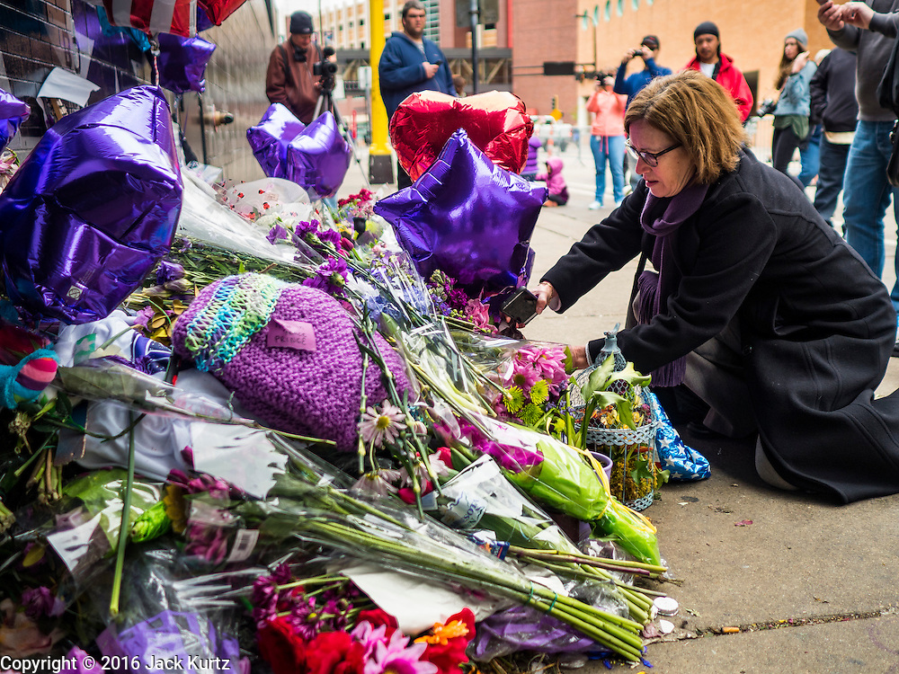 """22 APRIL 2016 - MINNEAPOLIS, MN:  A woman lays flowers at a memorial for Prince in front of 1st Ave in Minneapolis. Thousands of people came to 1st Ave in Minneapolis Friday, to mourn the death of Prince, whose full name is Prince Rogers Nelson. 1st Ave is the nightclub the musical icon made famous in his semi autobiographical movie """"Purple Rain."""" Prince, 57 years old, died Thursday, April 21, 2016, at Paisley Park, his home, office and recording complex in Chanhassen, MN.   PHOTO BY JACK KURTZ"""