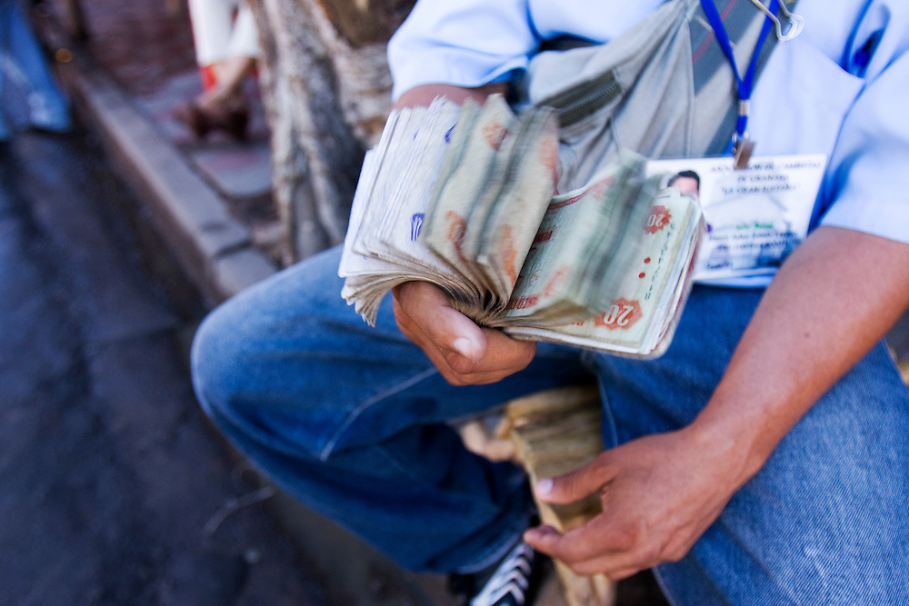 Changing dollars for Cordobas on the street in Granada, Nicaragua. A money changer flicks a fat wad of notes.