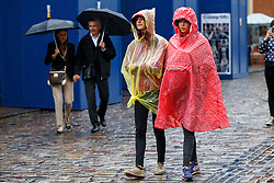 © Licensed to London News Pictures. 26/08/2015. London, UK. People shelter themselves during heavy rain in Covent Garden, London on Wednesday, August 26, 2015. Photo credit: Tolga Akmen/LNP