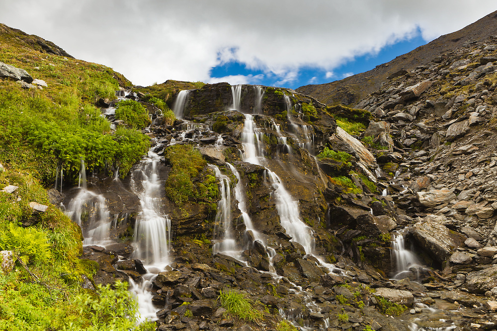 The stream from Summit Lake at Summit Lake State Recreation Site in Hatcher Pass cascades down a waterfall in Southcentral Alaska. Summer. Afternoon.