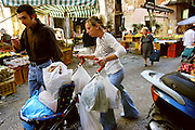 Pushing the week's worth of food in their 2-year-old son, Mauritio's stroller, Giuseppe Manzo and his wife Piera Marretta walk through Italy's Capo Market to their apartment in Palermo, Sicily. Normally, Piera, who shops every day, would purchase this much only on special occasions. Hungry Planet: What the World Eats (p. 178).