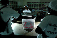 Poll workers prepare to open a ballot box to count the votes after the close of voting at a church in Monrovia, Liberia, October 11, 2005.