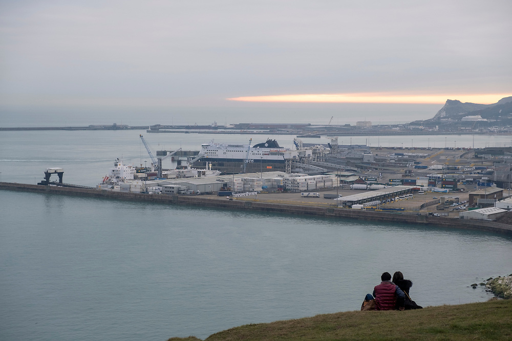 A couple sit and watch the Eastern Dock of the Port of Dover is where the cross channel port is situated with ferries departing here to go to Calais in France. Dover, Kent, United Kingdom.  Dover is the nearest port to France with just 34 kilometres (21 miles) between them. It is one of the busiest ports in the world. As well as freight container ships it is also the main port for P&O and DFDS Seaways ferries.  (photo by Andrew Aitchison / In pictures via Getty Images)