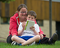 """Ryan Sasseville and his mom Kristina Eddy enjoy reading """"Diary Of A Wimpy Kid"""" together during Woodland Heights Elementary School's BBQ and Read In on Friday afternoon.  (Karen Bobotas/for the Laconia Daily Sun)"""