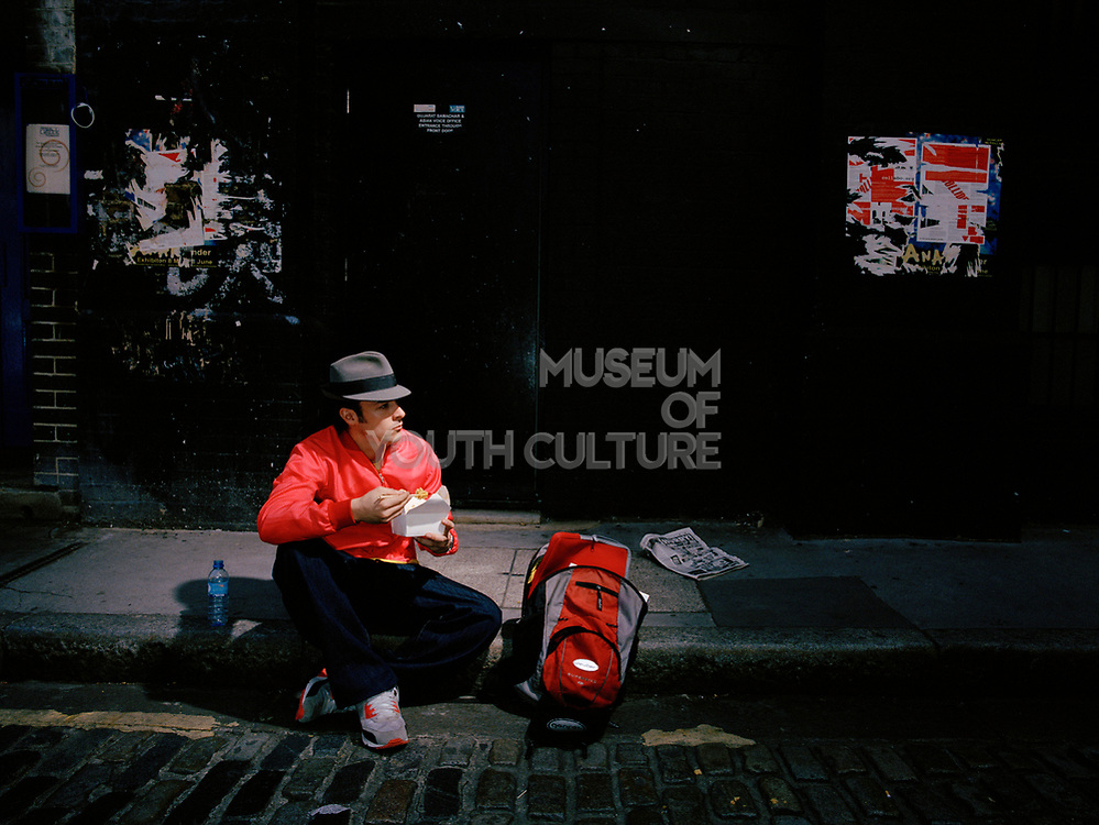 Young man sitting on pavement eating from take away container.