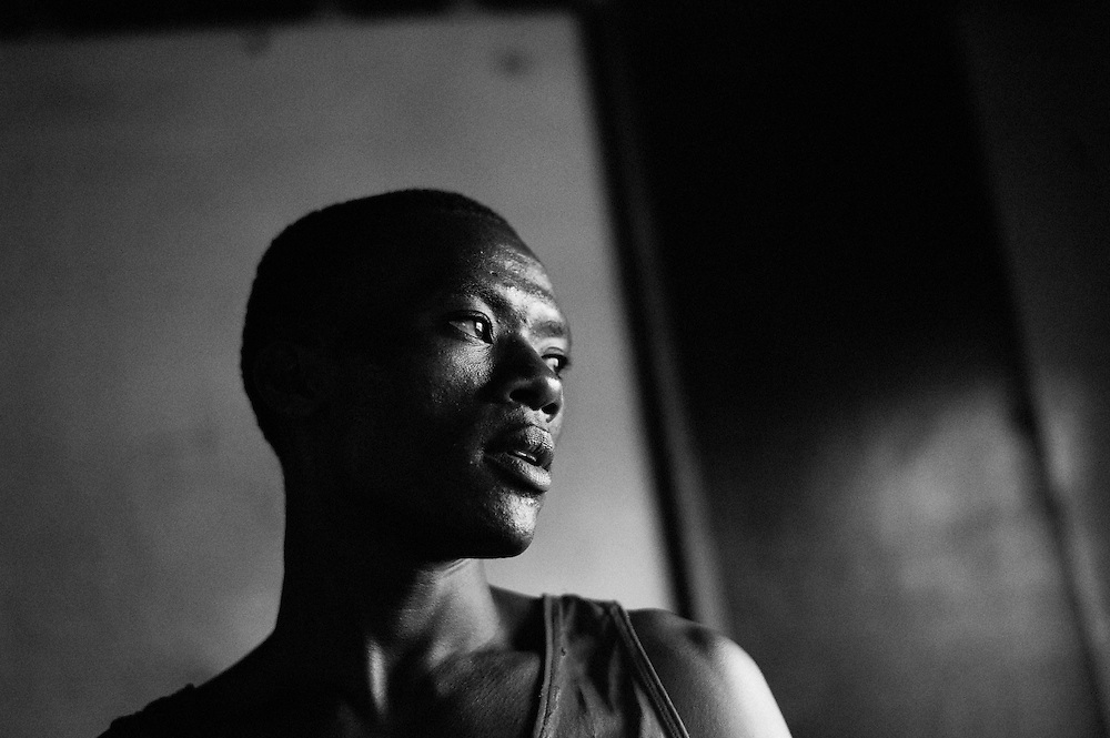 NAIROBI, KENYA - NOVEMBER 17, 2011: Kamau Ng'ang'a prepares for an Olympic Qualifying boxing bout. As a Kikuyu, Ng'ang'a represents the tribe that was targeted most violently during the post-election violence of 2008. Despite his tribal affiliation, Ng'ang'a is the club favorite and hopes to represent the Kibera Olympic Boxing Club in the 2012 Olympics.<br /> <br /> Within Kenya's progressive youth culture is the Kibera Olympic Boxing Club, a group of low-income adolescents from the slum whose leader uses boxing as a way to engage with idle youth. The group's ethnic diversity is remarkable given Kenya's 2008 post-election violence in which people from several tribes were forced violently out of slums. Together, these boxers represent a nascent trend of cross-tribe brotherhood in a healing nation.