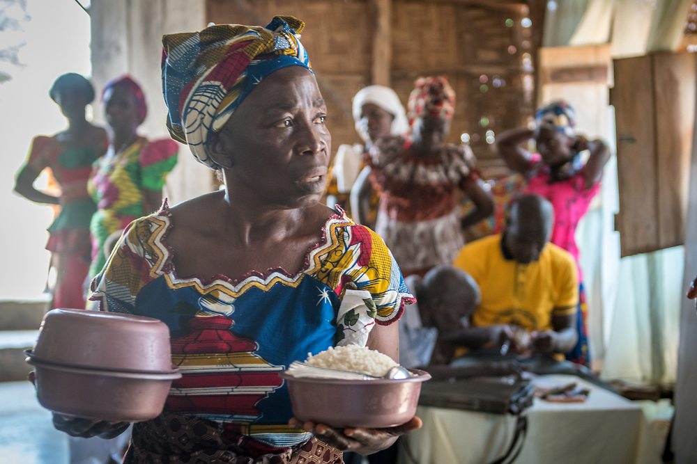 A woman holds bowls of food for a meal at church in Ganta, Liberia