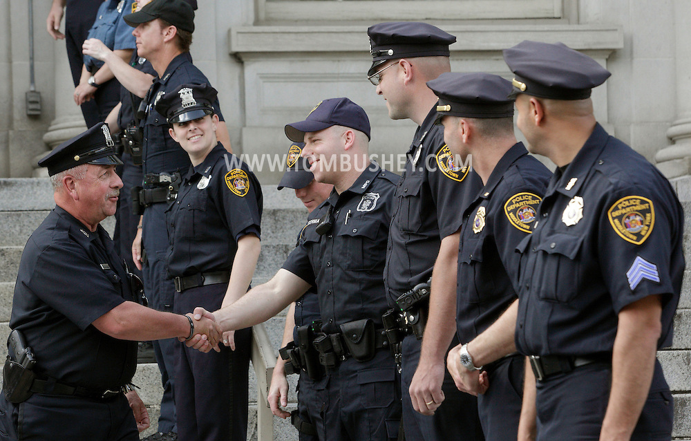 Middletown police officer Michael Canonico shakes hands with fellow officer Jason Berman in a ceremony marking the final day of Canonico's 32 years on the department.
