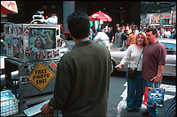 A couple is being photographed by a free photo booth in a New York street.
