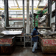 February 19, 2015 - New York, NY : Michael Brady uses a rake to manually direct physical waste -- mostly wet wipes -- into a bin for disposal at the Newtown Creek Wastewater Treatment Plant in  Greenpoint, Brooklyn, on Thursday afternoon. **This process is usually taken care of by a conveyor belt, but the belt was not functioning at the time.** Screens (not visible) filter large debris from raw sewage underground in the preliminary stage of the wastewater treatment process. Mechanical rakes then shuttle the debris above ground, where it is collected for disposal. While larger items occasionally make their way into the sewers via storm drains on the street, wet wipes make up the vast majority of the solid waste entering the city's sewage treatment system today. CREDIT: Karsten Moran for The New York Times