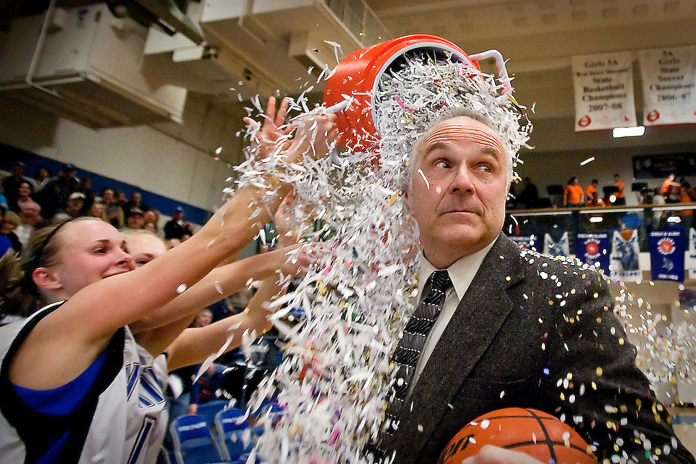 Coeur d'Alene High head coach Dale Poffenroth looks toward the crowd a moment before he is covered with confetti by Sadie Simon, a senior guard for the Vikings, following his team's 5A Region 1 championship win Friday over Post Falls High.