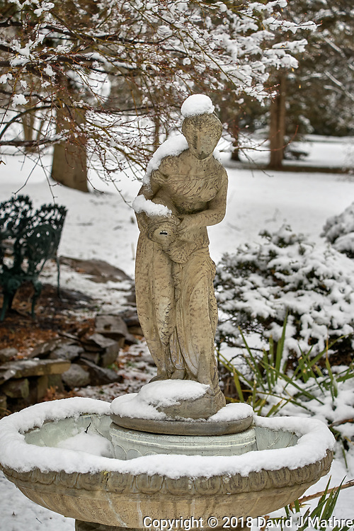 Birdbath statue with snow in April -- Winter is not gone. Image taken with a Leica TL2  camera and 60 mm f/2.8 lens (ISO 100, 60 mm, f/4.5, 1/200 sec).