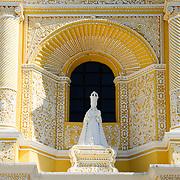 Alcove with stastue in the distinctive  and ornate yellow and white exterior of the Iglesia y Convento de Nuestra Senora de la Merced in downtown Antigua, Guatemala.