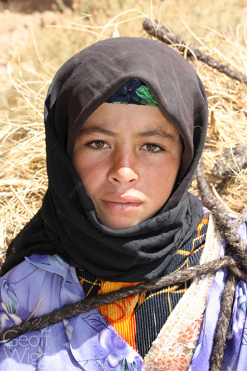 Nomad Berber girl in traditional clothing high in the Atlas Mountains Morocco