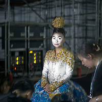 BEIJING, MAY -7, 2012 : a model waits to go on the catwalk. .Guo Pei , 45, is China's answer to haute couture. When she started out 15 years ago, there was no fashion in China . Since then though about everything in China has changed. Many more people are able to afford luxury products, and Chinese women, at least those who can afford it, follow international fashion trends. What makes Guo Pei different is what she puts on a runway. She employs 300 people in a workroom two hours from Beijing. She had to train them, but it?s also true that her creative freedom is tethered to relatively cheap labor. One dress alone, made entirely of golden panels, took 50,000 hours to embroider.
