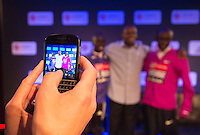Virgin Money London Marathon 2015<br /> <br /> A fan at a press conference takes a picture for social media featuring two of the the leading contenders for the London Marathon.<br /> Two of the top contenders pose with their coach.<br /> <br /> Left to right<br /> Emmanuel Mutai  Kenya<br /> Patrick Sang  (coach) Kenya<br /> Eliud Kipchoge  Kenya<br /> <br /> <br /> <br /> <br /> <br /> Photo: Bob Martin for Virgin Money London Marathon<br /> <br /> This photograph is supplied free to use by London Marathon/Virgin Money.