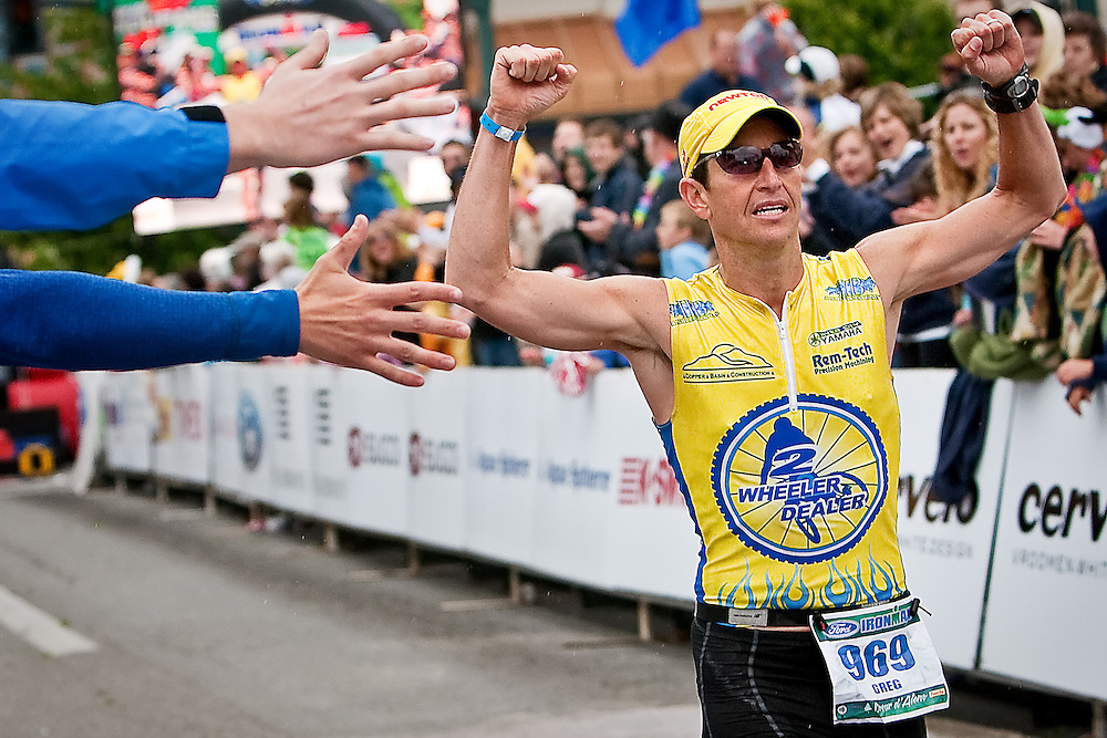 JEROME A. POLLOS/Press..Greg Gervais, from Coeur d'Alene, is cheered along the final stretch of the 140.6-mile course to finish as the top local Ironman with a time of 9:46:41.