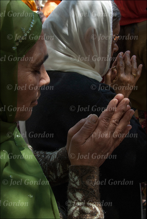 Close up of hands of Sikh-American women wearing sari or saree, praying before the start of the annual Sikh Day Parade in NYC.