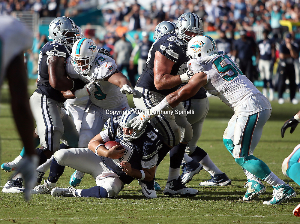 Dallas Cowboys quarterback Tony Romo (9) gets sacked by on a third down play in the fourth quarter by Miami Dolphins defensive end Derrick Shelby (79) Miami Dolphins defensive end Olivier Vernon (50) during the 2015 week 11 regular season NFL football game against the Miami Dolphins on Sunday, Nov. 22, 2015 in Miami. The Cowboys won the game 24-14. (©Paul Anthony Spinelli)