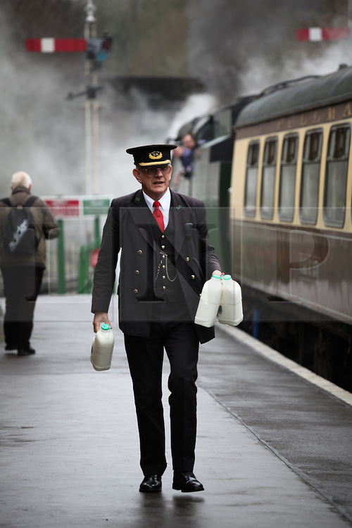 © Licensed to London News Pictures. 07/03/2014. Hampshire, UK. A station porter carrying a stock of milk for the steam train at Alresford Station today, 7th March 2014, which is the first day of the 'spring steam gala' on the Watercress Line. The railway line, operated by Mid Hants Railway Ltd, passes between Alresford and Alton in Hampshire. The line is named after its use in the past for transporting freshly cut watercress from the beds surrounding Alresford to London. Photo credit : Rob Arnold/LNP