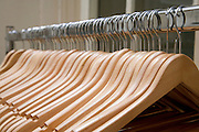 empty coat rack with many wooden clothing hangers