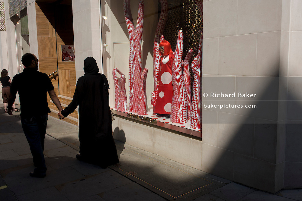 A Muslim couple walk hand in hand pass-by the Louis Vuitton shop window in New Bond Street. Holding hands, the man and woman show an unusual display of affection, not very much seen in the Muslim world. The red theme of the store window acts as a splash of vibrant colour in an otherwise neutral street landscape in central London. The design is a collaboration between Vuitton and the artist Yakoi Kusama, whose tentacle and flower campaign accompanies a life size Yayoi Kusama model.