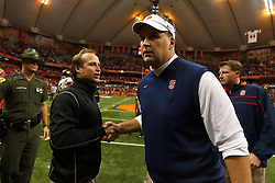 Oct 21, 2011; Syracuse NY, USA;  Syracuse Orange head coach Doug Marrone (right) shakes hands with West Virginia Mountaineers head coach Dana Holgorsen (left) after the game at the Carrier Dome.  Syracuse defeated West Virginia 49-23. Mandatory Credit: Jason O. Watson-US PRESSWIRE