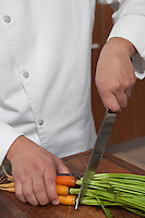 Mid- adult chef cutting carrots
