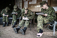 Young female police officers in military fatigue fill forms before leaving the base and going back to their academy. <br />