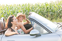 Happy female friends enjoying road trip in convertible