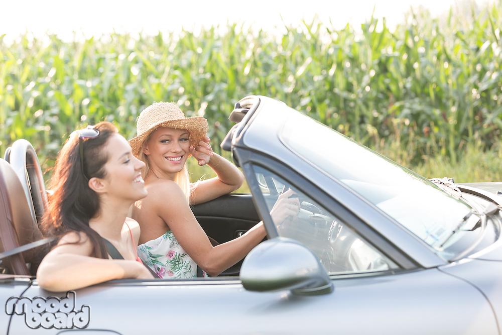 Happy female friends enjoying road trip in convertible