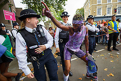 © Licensed to London News Pictures. 28/08/2016. London, UK. Police officers react to a dancer interacting with them whilst parading on family day of Notting Hill Carnival in west London, Sunday, 28 August 2016. Photo credit: Tolga Akmen/LNP